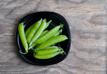 Top view. Fresh green peas in black bowl on wooden background.