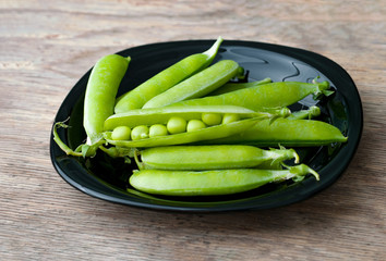Fresh green peas in black bowl on wooden background.