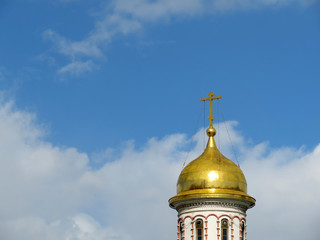 Dome with a cross of the Orthodox Church against the cloudy blue sky. Easter background
