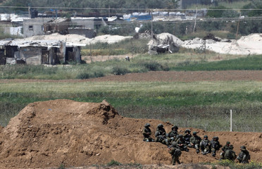 Israeli soldiers sit next to the border fence on the Israeli side of the border with the northern Gaza Strip, Israel