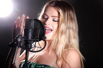 Junge Frau singt im Studio mit Emotionen