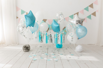 Festive background decoration for birthday celebration with gourmet cake and blue balloons in studio, cake smash first year concept
