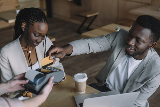 african american man paying for order with credit card while spending time with friend in cafe