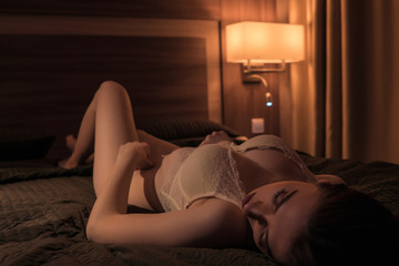 Young brunette with a sexy figure lies resting in bed