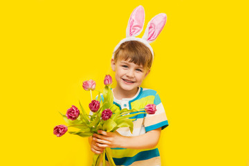 Cute positive little boy wearing bunny ears holding bouquet of flowers of tulips on a yellow background.