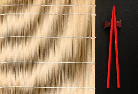 Red chopsticks and Bamboo mat on black table Top view with copy space