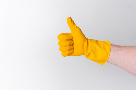 Cleaning concept - hand with cleaning gloves showing thumbs up isolated on white