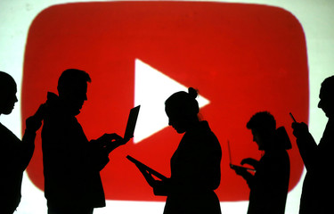 Silhouettes of laptop and mobile device users are seen next to a screen projection of Youtube logo in this picture illustration
