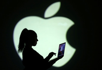 Silhouette of laptop user is seen next to a screen projection of Apple logo in this picture illustration