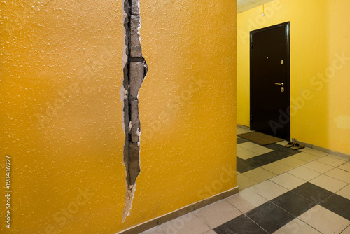 A crack in the wall of the apartment building. Yellow wall in the ...