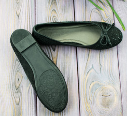 black suede female ballet flats on a wooden background