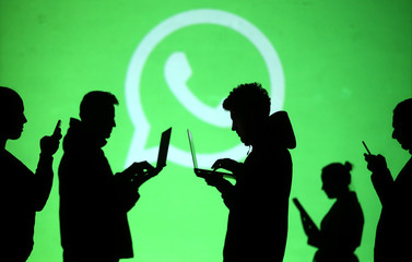 Silhouettes of laptop and mobile device users are seen next to a screen projection of Whatsapp logo in this picture illustration
