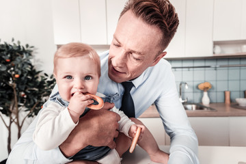 Sweet baby. Attentive businessman embracing his kid and bowing head while looking at little hand