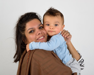 Smiling south asian mother holding her eurasian baby