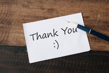 White paper note written word THANK YOU. Appreciation concept