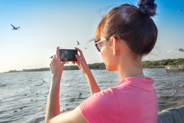 Tourist Asian woman shooting photo by her smart phone at sea with seagull birds and  blue cloud sky.