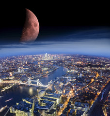abstract scene of London city at night with moon added from another photo made with telephoto lens