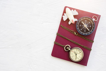 Travel background concept. Compass, pocket watch and airplane on red passport on white table. Picture for add text message. Backdrop for design art work.