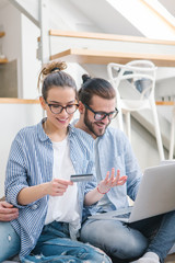 Young couple paying bills with credit card