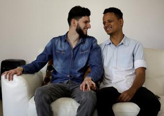 Gay couple Roberth Castillo and Mario Arias, pose for a photo at home in San Jose