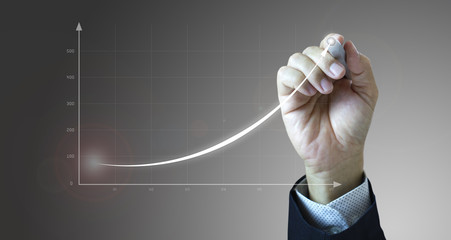 Close up of a businessman's hand drawing an exponential line curve showing of business growth and success rapidly.