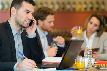 attractive businessman using mobile phone while having lunch
