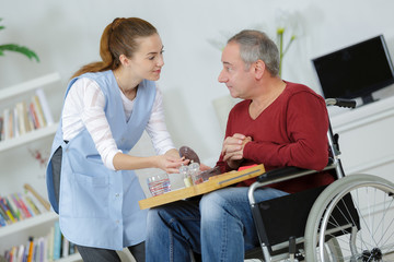 nurse with middle age man patient sitting on a wheelchair