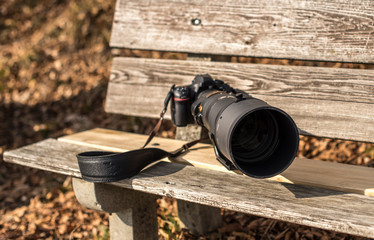 professional photo camera with big zoom lens on the bench