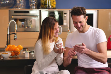 A couple in the kitchen looks at the smart phone with the souvenir photos of their holidays or of the past times while having breakfast and smiling happily. Concept of: family, technology, memories
