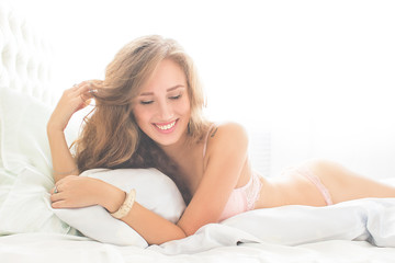 happy pretty blond girl lying in bed in early morning