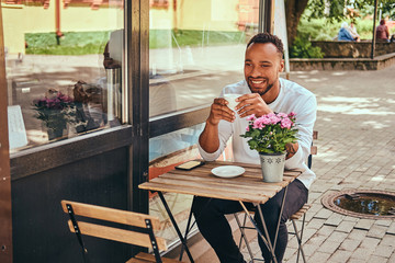A fashionable African-American bearded male sitting near a coffee shop with a cup of coffee.