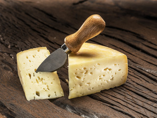 Fototapete - Pieces of homemade cheese on the wooden background.