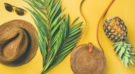 Wall Mural - Colorful summer female fashion outfit flat-lay. Straw sunhat, bamboo bag, sunglasses, palm branches and pineapple over yellow background, top view, wide composition. Summer vacation fashion concept