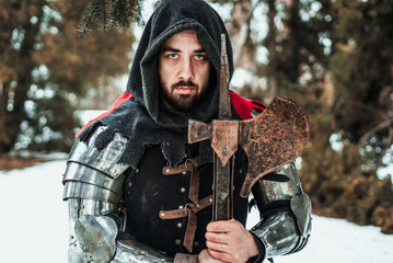 man knight in historical clothing with an ax