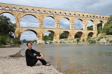 Young woman near Aqueduct Pont du Gard,the bridge on river Gardon, Provence, France