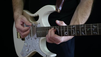 A man is playing a rhythm on a white electric guitar on a black background - 2. Professional guitar playing.