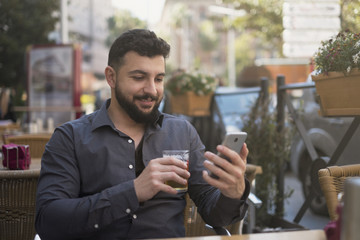 Bearded man looking smartphone in bar terrace while drinking beer