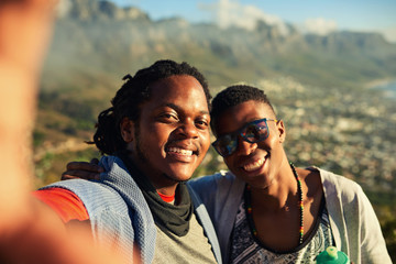Two happy male african friends take a selfie together while hiking outdoors with gorgeous mountains in the background and true emotion in their smiles.