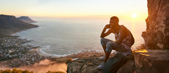 Panoramic image of a young black man sitting on the top of a mountain talking on a mobile phone during an amazing sunset, with a beautiful view of the ocean and cityscape in the background.