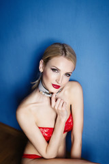 girl in red lingerie with a collar on a blue wall background
