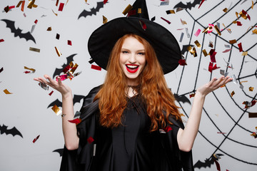 Halloween Witch Concept - Happy elegant witch throwing confetti for celebrating halloween party over bat and spider background. Wall mural