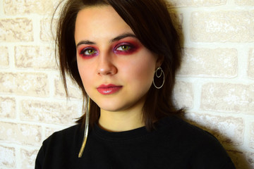 Portrait of the young beautiful girl with green eyes and a bright creative make-up in lilac tones. Сloseup.