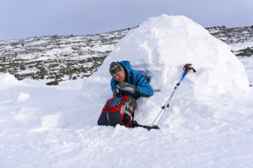 hiker pours himself a tea from a thermos, sitting in a snowy house igloo against a background of a winter mountain landscape