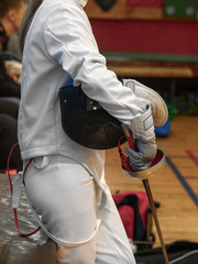 A teenage girl at a sword-fencing competition stands holding a mask under her arm, and a sword in her hand. Waiting for the next fight.