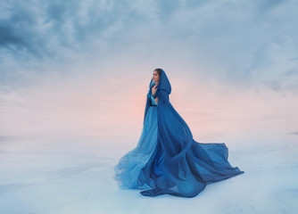 The Snow Queen in a blue raincoat that flutters in the wind. A traveler on a background of sunrise or sunset, and a frozen valley covered with snow and clouds, a place where heaven meets the earth.