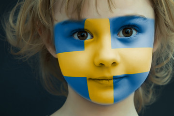 Portrait of a child with a painted Sweden flag