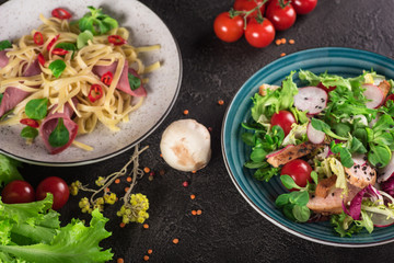 Delicious dinner. Italian pasta and fresh vegetable salad on the black background. Healthy food. Close up. Top view