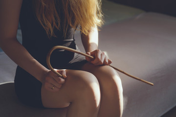 Woman with rattan school cane. Strict woman domination. BDSM concept. Adult role game concept