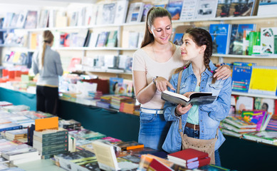 glad woman showing open book to cheerful girl in book boutique