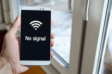 A person sees a white inscription on a black smartphone display that holds in his hand. No signal